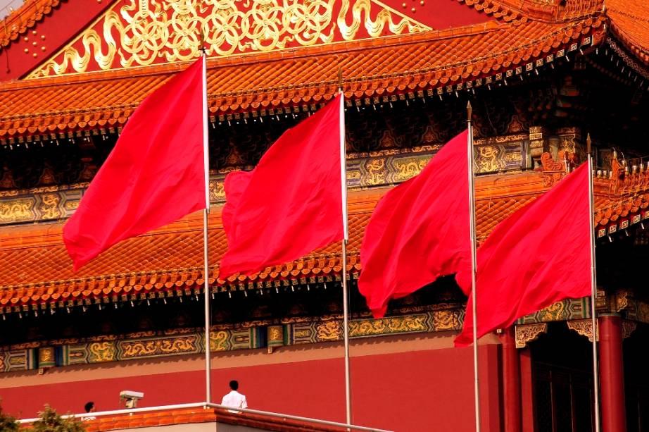 """Segunda maior economia do mundo, a China possui uma economia de mercado fortemente regulada pelo governo, que investe pesado em áreas que considera essenciais. Por anos à sombra da bandeira socialista de Mao Tsé-Tung, o país começou uma onda de empreendedorismo avassaladora na esteira da famosa frase do líder Deng Xiaoping: """"Enriquecer é glorioso"""". Na foto, bandeiras junto ao Portão da Paz Celestial, em Pequim"""