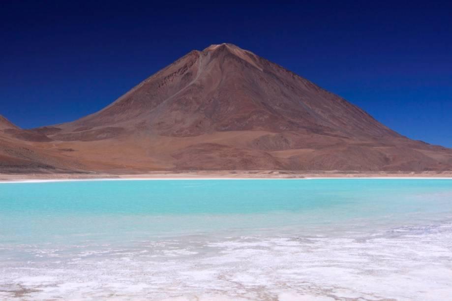 Localizado a 4000 metros de altitude, a Laguna Verde possui esse tom por conta de traços de cobre oxidados. O vulcão Licanbur é um dos muitos que pontilham o altiplano boliviano