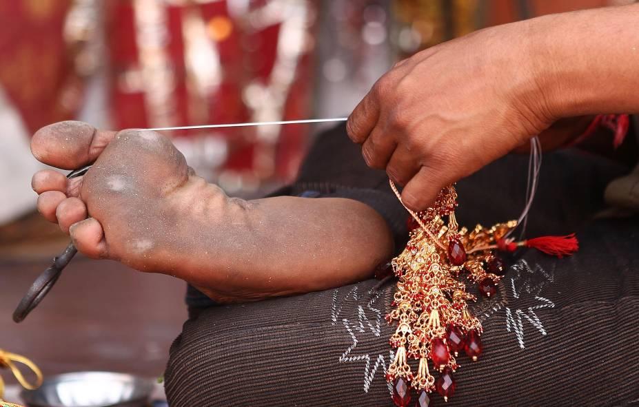 Artesão confecciona bijuteria com uma ajudinha do pé, no centro de Jaipur