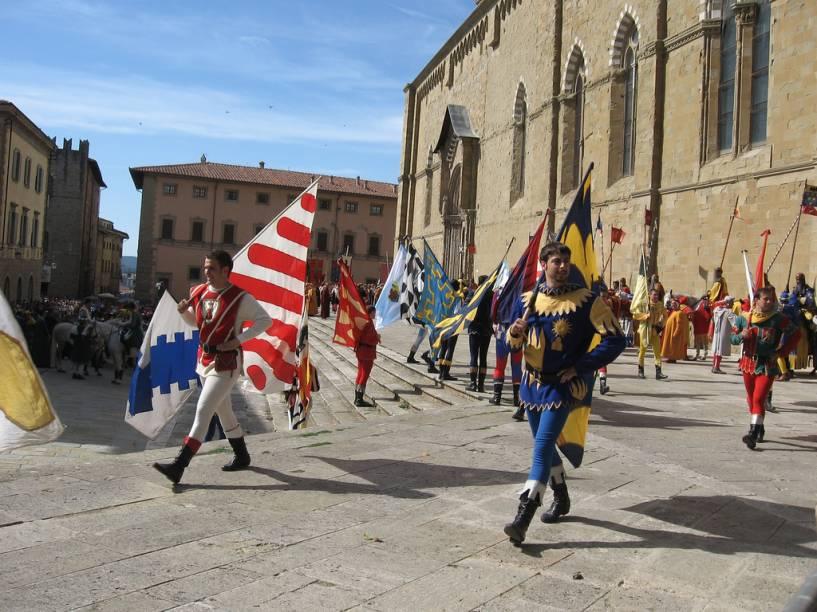 """<strong>AREZZO</strong> (a 81 km de Montalcino)        Em <strong><a href=""""http://viajeaqui.abril.com.br/cidades/italia-arezzo"""" rel=""""Arezzo """" target=""""_blank"""">Arezzo</a></strong>, você receberá um verdadeiro banho de arte – de fato a cidade está incluída entre as chamadas Cidades da Arte.        De origem etrusca, como a maioria das cidades toscanas, hoje é constituída de uma parte moderna e de um centro histórico ainda em grande parte cercado por muralhas que protegem seu patrimônio artístico.        No passado foi célebre pela produção de cerâmica artística, especialmente os famosos vasos aretinos. A colina do <em>Duomo</em> domina a cidade embelezada pelo jardim público conhecido como <em>Passeggio del Prato</em> (Passeio no Prado) – herança da época áurea do domínio da mais famosa família florentina: os Medici.        Até hoje mantém uma tradição popular originária da Idade Média: a <a href=""""http://www.giostradelsaracino.arezzo.it"""" rel=""""Giostra del Sarracino"""" target=""""_blank""""><em>Giostra del Sarracino</em></a>.O evento se realiza em duas datas todos os anos<em>: Giostra di San Donato</em> em 23 de junho, <em>e Giostra della Madonna del Conforto</em> em 2 de setembro.        Para fechar com chave de ouro o seu itinerário pela Toscana, nada melhor do que esta parada em Arezzo para admirar a <em>Piazza Grande</em> e o seu conjunto arquitetônico perfeito, que inclui a Loggia Vassari, cuja fachada foi criada por Giorgio Vassari, a igreja de San Domenico – para admirar um crucifixo de autoria do pintor Cimabue –, a Chiesa di San Francesco, que conserva os esplendidos afrescos de Piero della Francesca e a Pieve di Santa Maria, a mais bonita igreja medieval da cidade.        Com o olhar cheio de muita beleza e o doce sabor do bom vinho na boca, você pode voltar para Florença, a apenas 73 quilômetros de Arezzo. <em>Arrivederci a presto!</em>"""