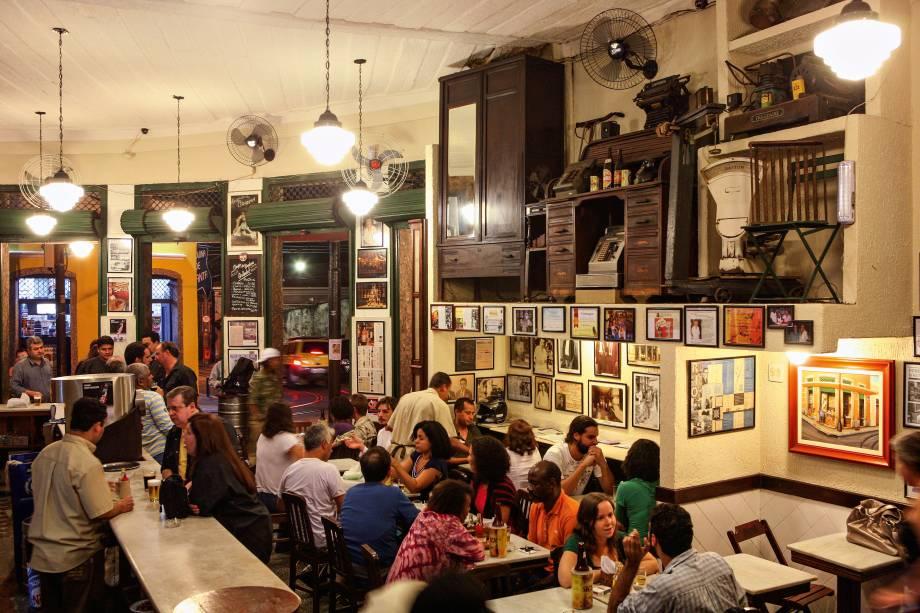 """<strong>PARA CURTIR O CENTRO E ARREDORES</strong> <strong><a href=""""http://armazemsaothiago.com.br/"""" target=""""_blank"""" rel=""""noopener"""">Armazém São Thiago</a></strong>O sobrado cor-de-rosa, localizado em uma bucólica esquina, anuncia na fachada o ano de inauguração (1919) e preserva no interior um dos ambientes mais deliciosamente old school de Santa Teresa, na região central do <a href=""""http://viajeaqui.abril.com.br/cidades/br-rj-rio-de-janeiro"""" target=""""_blank"""" rel=""""noopener"""">Rio</a>. A geladeira de madeira, o balcão de mármore e os armários de peroba escura evocam uma atmosfera de antigamente e compõem a decoração do estabelecimento, que nasceu como empório de produtos finos e artigos importados (e é conhecido como Bar do Gomez, em referência ao espanhol José Gomez Cantorna, que esteve à frente do negócio). A casa serve chope, cerveja, boa variedade de cachaças e petiscos como carne-seca acebolada com aipim frito <em>R. Áurea, 26 (Santa Teresa), (21) 2232-0822</em>"""