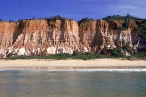 A Praia da Pitinga é versátil, no canto esquerdo ficam as barracas que garantem o movimento, do outro lado, as falésias dominam o cenário, deserto e com mar calmo