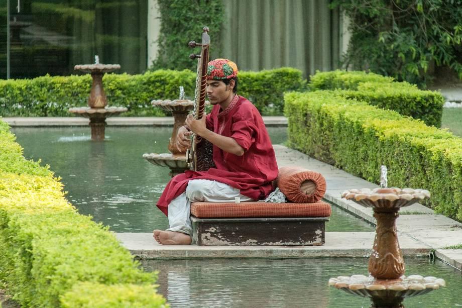 Um músico toca a cítara enquanto os hóspedes meditam no jardim do hotel Rambagh Palace, em Jaipur