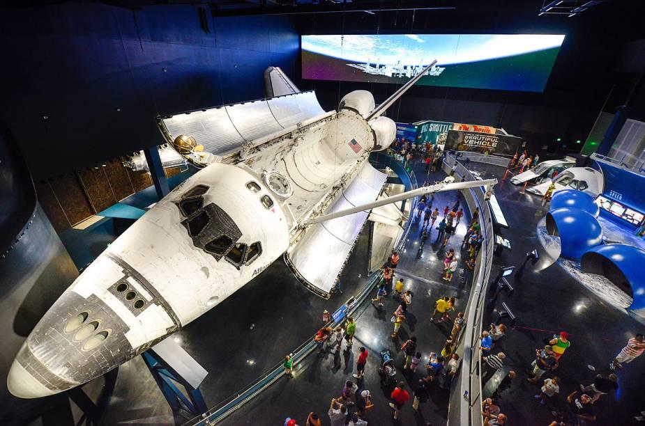 Visitantes admiram o ônibus espacial Atlantis, em exibição com os braços mecânicos que consertaram o telescópio Hubble em 2009