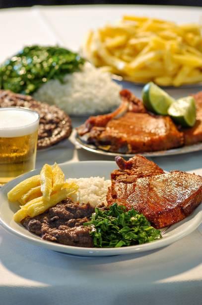 """<strong>PARA CURTIR O CENTRO E ARREDORES</strong> <strong><a href=""""https://pt-br.facebook.com/barbrasil.alemaodalapa/"""" target=""""_blank"""" rel=""""noopener"""">Bar Brasil</a> </strong>A cozinha germânica é um traço em comum no cardápio de alguns endereços centenários do <a href=""""http://viajeaqui.abril.com.br/cidades/br-rj-rio-de-janeiro"""" target=""""_blank"""" rel=""""noopener"""">Rio</a>. É o caso do <a href=""""http://viajeaqui.abril.com.br/estabelecimentos/br-rj-rio-de-janeiro-restaurante-bar-luiz"""" target=""""_blank"""" rel=""""noopener"""">Bar Luiz</a> e também do Bar Brasil – aberto em 1907 com o nome de Bar Zeppelin e rebatizado na época da Segunda Guerra Mundial. Receitas vigorosas, como kassler (costela suína defumada) e eisbein (joelho de porco), vão à mesa na companhia de salada de batata, chucrute e do chope cremoso. O sobrado tem portas e biombos de madeira escura e duas entradas, uma pela Mem de Sá e outra pela Rua do Lavradio, que reúne antiquários e é opção para um passeio depois do almoço. A poucos metros fica o Nova Capela (R. Mem de Sá, 96), célebre pelo cabrito com alho frito e arroz de brócolis <em>Av. Mem de Sá, 90 (Lapa), (21) 2509-5943</em>"""