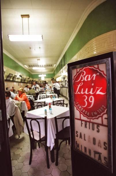 """<strong>PARA CURTIR O CENTRO E ARREDORES</strong> <strong><a href=""""https://pt-br.facebook.com/restaurantebarluiz/"""" target=""""_blank"""" rel=""""noopener"""">Bar Luiz</a> </strong>Decano da boemia carioca, foi inaugurado em 1887 – antes da Abolição da Escravatura e da Proclamação da República. Naqueles tempos, ficava na Rua da Assembleia e era conhecido como """"Braço de Ferro"""" devido ao costume do dono, o alemão Adolf Rumjaneck, de desafiar os fregueses na queda de braço para promover o consumo do chope (então menos prestigiado do que o vinho). O estabelecimento mudou-se para o endereço atual em 1927, como Bar Adolf, e foi rebatizado nos anos 1940, quando estudantes tentaram destruir o local numa manifestação contra o fascismo – o bar foi salvo pela intervenção do compositor (e cliente) Ary Barroso. A partir daí virou Bar Luiz, aportuguesando o nome do proprietário da época, Ludwig Vöit. A origem germânica da casa faz-se ainda hoje presente na cozinha, de onde saem pedidos tradicionais como salada de batata, kassler e salsichão <em>R. da Carioca, 39 (Centro), (21) 2262-6900</em>"""