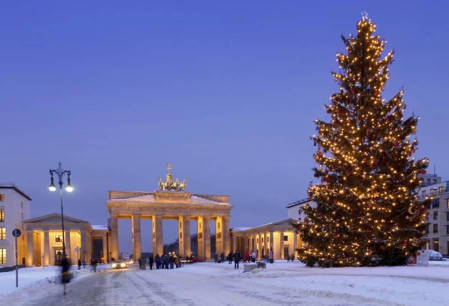 No fim do ano, o inverno chega à Berlim, junto com a neve; na foto, o Portão de Brandemburgo ao lado de uma árvore de Natal gigantesca