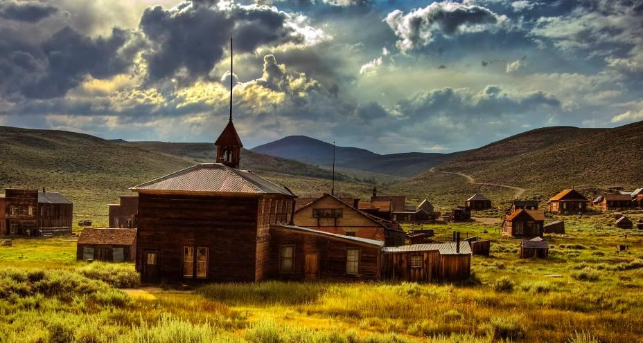 """<strong>Vilarejo de Bodie, Califórnia, <a href=""""http://viajeaqui.abril.com.br/paises/estados-unidos"""" rel=""""Estados Unidos"""" target=""""_blank"""">Estados Unidos</a></strong>    Localizada na região de Serra Nevada, essa pequena vila com clima de Velho Oeste faz parte de um conjunto de mais de seis mil cidades-fantasmas de extrema importância para a cultura nacional. Todas elas, aliás, foram fundamentais para o desenvolvimento da Corrida de Ouro e de metais preciosos no final do século 19. Bodie, em particular, soube preservar suas características mesmo depois do abandono por parte de seus moradores, que deixaram suas casas para trás depois que o comércio e exploração de metais começou a degringolar, e dos atos de vandalismo e incêndios. As casas de madeira, a decoração e os objetos pessoais da população encontram-se bem preservados e conferiram três títulos de respeito para a vila que, no passado, foi marcada como segundo centro urbano mais importante da Califórnia, atrás somente de <a href=""""http://viajeaqui.abril.com.br/cidades/estados-unidos-los-angeles"""" rel=""""Los Angeles"""" target=""""_blank"""">Los Angeles</a>: o de Registro Nacional de Lugares Históricos, o de Distrito Histórico Nacional dos Estados Unidos e de Marco Histórico da Califórnia"""