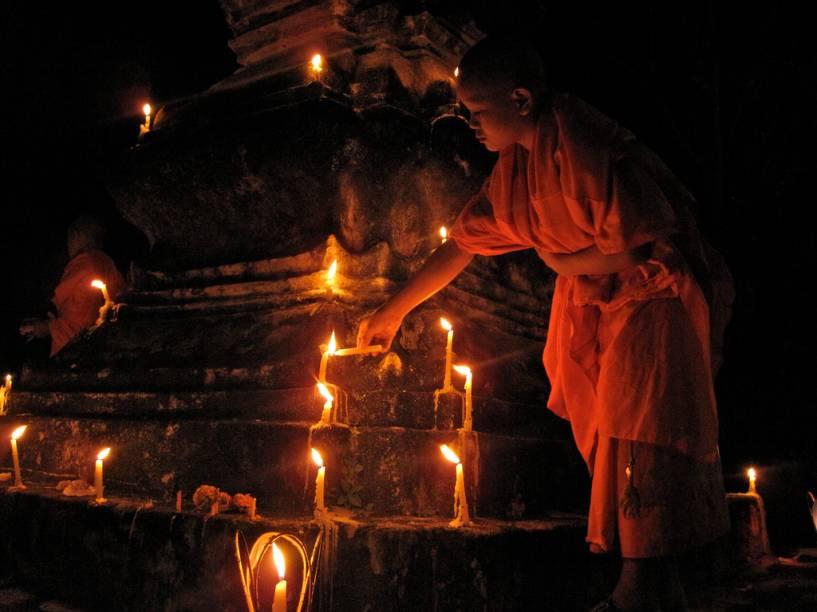 Aprendiz de monge acende vela durante o FEstiva Boun Ok Phansa, em Luang Prabang