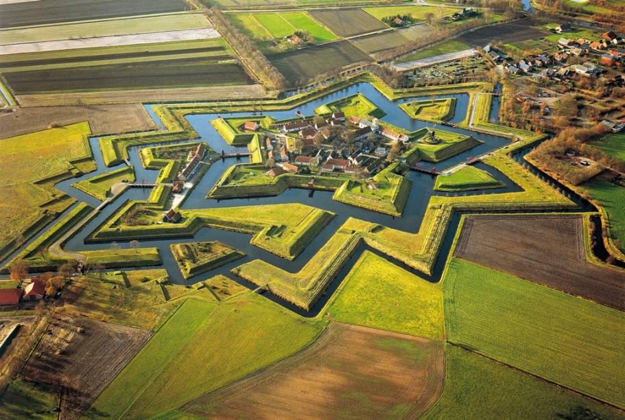 """<strong>Bourtange, <a href=""""http://viajeaqui.abril.com.br/paises/holanda"""" rel=""""Holanda"""" target=""""_blank"""">Holanda</a></strong>                            No norte da <a href=""""viajeaqui.abril.com.br/paises/holanda"""">Holanda</a>, uma pequena cidade na província de Groningen, junto à fronteira com a <a href=""""viajeaqui.abril.com.br/paises/alemanha"""">Alemanha</a>, guarda uma joia da engenharia militar. Construída sob as ordens de Guilherme de Orange – os holandeses vestem laranja em homenagem a esta dinastia – seu sistema defensivo de bastiões, muros, torres e fossos só pode ser claramente apreciado quando visto do alto. Os conceitos utilizados nesta fortaleza foram adotados em construções pernambucanas erguidas pelos holandeses, como o <a href=""""http://viajeaqui.abril.com.br/estabelecimentos/br-pe-itamaraca-atracao-forte-orange"""">Forte Orange</a>, em <a href=""""http://viajeaqui.abril.com.br/cidades/br-pe-itamaraca"""">Itamaracá</a>, e o <a href=""""http://viajeaqui.abril.com.br/estabelecimentos/br-pe-recife-atracao-forte-das-cinco-pontas"""">Forte de Cinco Pontas</a>, em <a href=""""http://viajeaqui.abril.com.br/cidades/br-pe-recife"""">Recife</a>"""