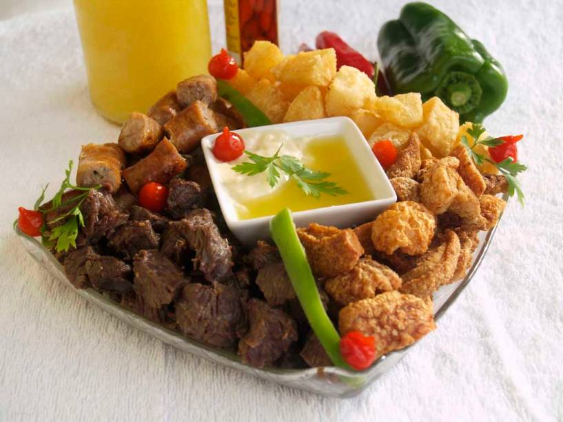 """O petisco Quarteto Fantástico, servido na casa <strong>Buteco de Minas</strong>, em <a href=""""http://viajeaqui.abril.com.br/cidades/br-am-manaus"""" rel=""""Manaus"""" target=""""_blank""""><strong>Manaus</strong></a>, é composto por torresmo, carne de sol, linguiça de porco, mandioca com manteiga de garrafa e creme de jiló. <em>Avenida das Flores, 318, Conjunto Tiradentes, Aleixo, (92) 3248-0130, 2ª/sáb 17h/0h.</em>"""