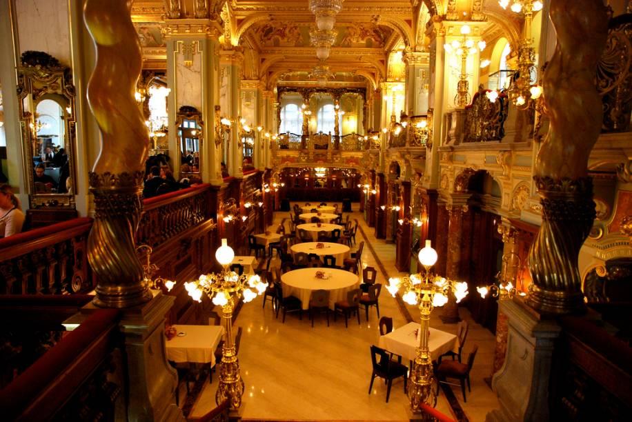 """<strong>Cafe New York, Hungria</strong><br />    Foi inaugurado em outubro de 1894 como """"o mais belo café do mundo"""". Seu interior esbanjava mármore, bronze, cristais, afrescos, luminárias e estofados em seda e veludo em estilo eclético que se aproximava do barroco. Ponto de encontro da elite húngara, ali se reuniam os círculos culturais e mundanos de <a href=""""http://viajeaqui.abril.com.br/cidades/hungria-budapeste"""" rel=""""Budapeste"""" target=""""_blank""""><strong>Budapeste</strong></a>. Era o lugar perfeito para discutir ideias, saber as últimas novidades e, muito importante, ver e ser visto.<br />    <br />    Na década de 1910, além de seu público tradicional de intelectuais e jornalistas, foi ponto de encontro para cineastas como Alexander Korda, que então iniciava a sua carreira. A cidade chegou a ter 500 cafés entre 1910 e 1930. A deles maioria oferecia papel e tinta gratuitamente, além de um cardápio especial para escritores, a preço reduzido.<br />    <br />    Conta-se que o escritor húngaro Ferenc Molnár, que fazia da sua mesa no café seu local de trabalho, pretendendo que o mesmo ficasse aberto durante 24 horas, se apoderou da chave da porta e jogou-a no Danúbio para que nunca fosse fechada. Grande parte desses locais foi destruída durante a Segunda Guerra, outros não sobreviveram ao regime comunista e às crises financeiras. A partir de 2006, inteiramente restaurado e com muitas peças autênticas recuperadas, o <a href=""""http://viajeaqui.abril.com.br/estabelecimentos/hungria-budapeste-restaurante-cafe-new-york"""" rel=""""Café New York"""" target=""""_blank""""><strong>Cafe New York</strong></a> voltou a ostentar o luxo e o brilho de outros tempos"""