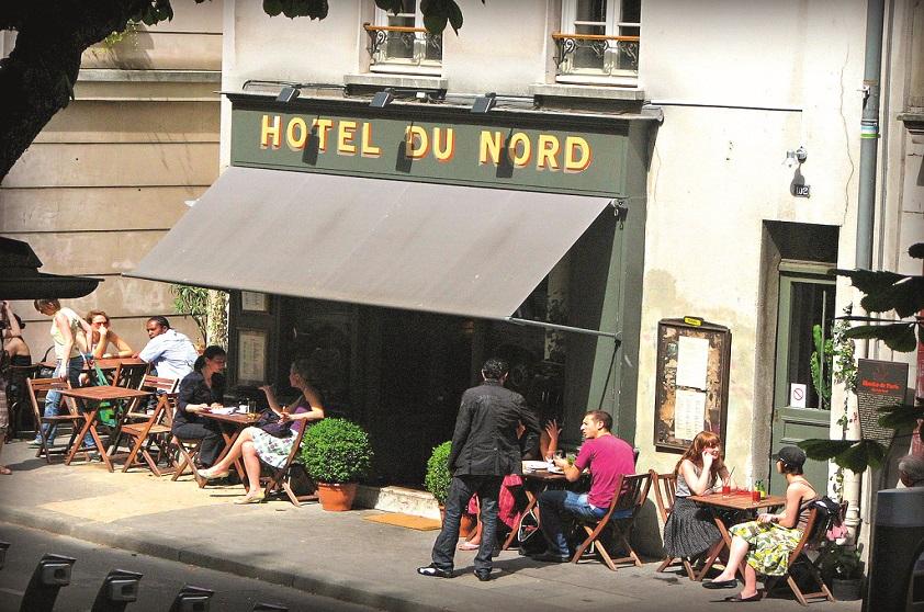 """Uma das referências lendárias da região, o bar e restaurante<a href=""""http://www.hoteldunord.org/en/"""" rel="""" Hôtel du Nord """" target=""""_blank""""> Hôtel du Nord </a>deve o nome à sua origem como hotel mesmo. Inaugurado em 1885, era frequentado por prostitutas e operários, chamado de <em>l'hotel de poux volants</em> (""""hotel dos piolhos voadores""""). Em 1938, foi cenário do filme homônimo do francês Marcel Carné. Nos anos 80, fechou as portas e foi reaberto no atual formato em 1993, com mesas abrigadas sob a fachada tombada. Dá para fazer uma refeição nos salões escurinhos ou ficar do lado de fora, sempre uma opção convidativa no Canal Saint-Martin."""