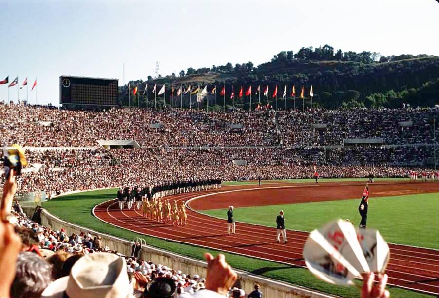 """<strong>14.<a href=""""http://viajeaqui.abril.com.br/cidades/italia-roma"""" target=""""_blank"""" rel=""""noopener"""">Roma</a>, <a href=""""http://viajeaqui.abril.com.br/paises/italia"""" target=""""_blank"""" rel=""""noopener"""">Itália</a>, 1960</strong> Lá em 1908, Roma tinha perdido a oportunidade de sediar as Olimpíadas por causa da erupção do vulcão Vesúvio. Depois de 52 anos, o tão esperado momento chegou com a cerimônia de abertura (foto), em 25 de agosto. Toda a competição foi marcada pela utilização de pontos turísticos que remetiam à Roma Antiga para o transcorrer das modalidades esportivas, como o Arco e a Basílica de Constantino, as Termas de Caracala e as ruínas do Foro Romano."""
