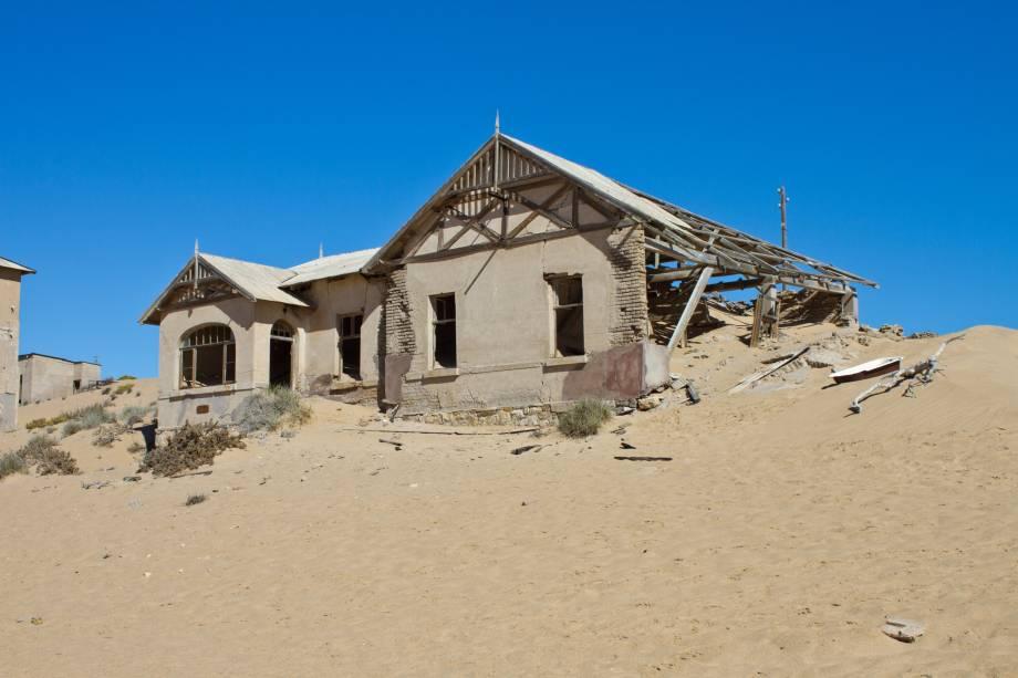 <strong>Cidade Fantasma de Kolmanskop, Namíbia</strong>    Os desertos africanos possuem um fascínio que desperta a curiosidade dos visitantes, sobretudo o Mar de Areia da Namíbia, tombado pela Unesco em 2013 como Patrimônio Mundial. Foi a areia, aliás, a responsável por engolir as casas construídas na cidade de Kolmanskop. No início de 1900, a região foi ocupada pelos alemães, que viram nela a chance de enriquecer graças à exploração de diamantes. O excesso da atividade, no entanto, fez com que os minérios sofressem um forte esgotamento. Na década de 1950, o abandono por parte de seus moradores fez com que a constante limpeza da areia insistente que ocupava as suas ruas fosse completamente abandonada. Hoje, o governo mantém a região habitável para que os turistas curiosos que passeiam por ali possam continuar a explorar a área