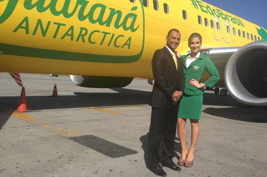 Cafu e Claudia Leitte posam na frente do avião verde e amarelo do Guaraná