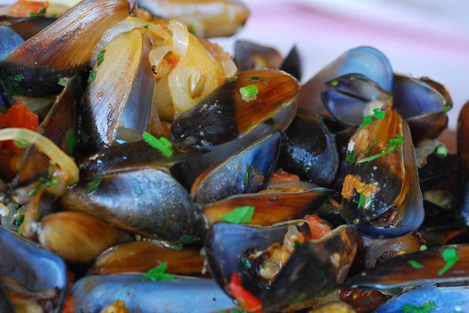 """<strong>Marisco lambe-lambe</strong> A farta porção dos pequenos moluscos, cozidos em molho à base de vinho branco, tomate, alho, cebola e azeite, tornou-se um delicioso motivo de parada na matriz do restaurante <a href=""""http://viajeaqui.abril.com.br/estabelecimentos/br-sp-bertioga-restaurante-dalmo-barbaro"""" target=""""_blank"""" rel=""""noopener"""">Dalmo Bárbaro</a>, na Baixada Santista, em São Paulo. Para muitos habitués, o prato, servido desde 1963, faz parte das memórias de infância. Com o tempo, a fama da receita passou a ser disputada por outras casas da região, como o Joca, que chega a vender 1 tonelada de marisco em um fim de semana. <strong>Quem prepara:</strong> <a href=""""http://www.dalmobarbaro.com.br/"""" target=""""_blank"""" rel=""""noopener"""">Dalmo Bárbaro</a> e <a href=""""http://www.jocarestaurante.com.br/"""" target=""""_blank"""" rel=""""noopener"""">Restaurante do Joca</a>, no <a href=""""http://viajeaqui.abril.com.br/cidades/br-sp-guaruja"""" target=""""_blank"""" rel=""""noopener"""">Guarujá (SP)</a>"""