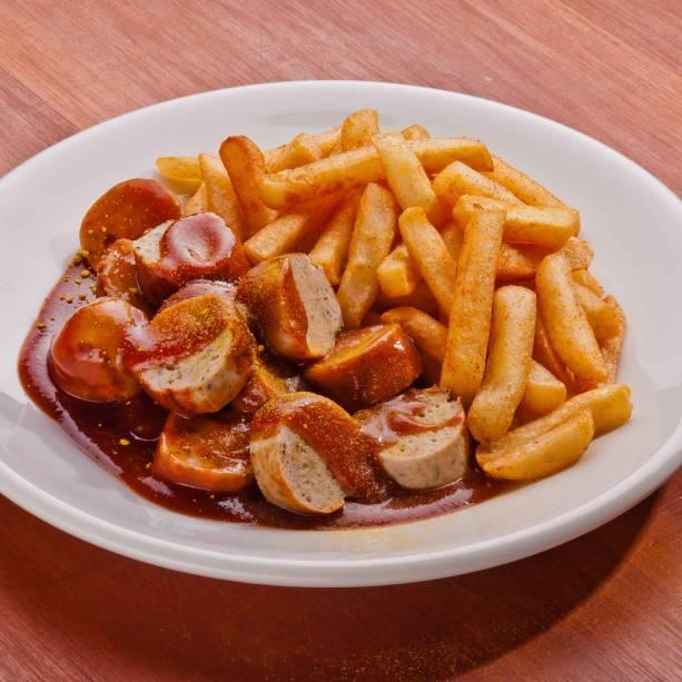 Currywurst, fast-food alemão, com batatas fritas e salsicha de porco fatiada, coberta por catchup ao curry