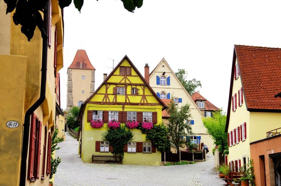 """Ela é popularmente conhecida como a """"cidade das 20 torres"""" e também fica na rota romântica da Baviera. Com pouco mais de 11 mil habitantes, a cidade tem um dos complexos medievais mais bem conservados da Alemanha. Lendas locais contam que ela teria passado intacta à Guerra dos Trinta Anos em 1632, quando crianças interferiram na ocupação sueca e imploraram que a região ficasse imune às depredações. Vinícolas, igrejas e ruas tranquilas complementam seus atrativos, também reforçados pela ótima hospitalidade dos moradores locais.<a href=""""http://www.booking.com/city/de/dinkelsbuhl.pt-br.html?aid=332455&label=viagemabril-vilasalemanha"""" target=""""_blank"""" rel=""""noopener""""><em>Busque hospedagens em Dinkelsbühl no Booking.com</em></a>"""