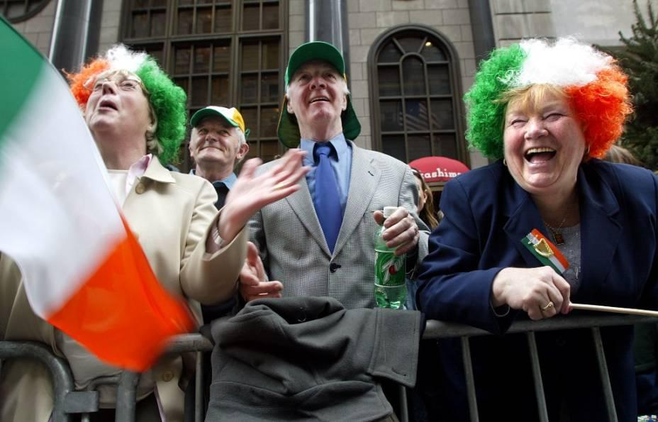 """A diáspora irlandesa, iniciada com as desastrosas colheitas do século 19, seguida de fome, levou milhares de pessoas a imigrarem pelo mundo. O ex-presidente John Kennedy e a atriz Grace Kelly são só alguns dos descendentes desses imigrantes, muitos dos quais comemoram ativamente o Dia de Saint Patrick, patrono da <a href=""""http://viajeaqui.abril.com.br/paises/irlanda"""" target=""""_blank"""">Irlanda</a>, no dia 17 de março.Na foto, pessoas assistem a parada comemorativa em <a href=""""http://viajeaqui.abril.com.br/cidades/irlanda-dublin"""" target=""""_blank"""">Dublin</a>. De errado, só a bebida na mão do senhor ao centro. Podia ser uma Guinness, mas pelo menos a garrafa é verde"""