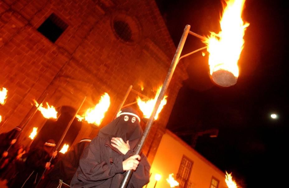Um farricoco (fiel encapuzado) carrega uma tocha durante a Procissão do Fogaréu, em Guimarães, Portugal. A celebração dramatiza a perseguição e prisão de Cristo, às 0h da quinta-feira santa