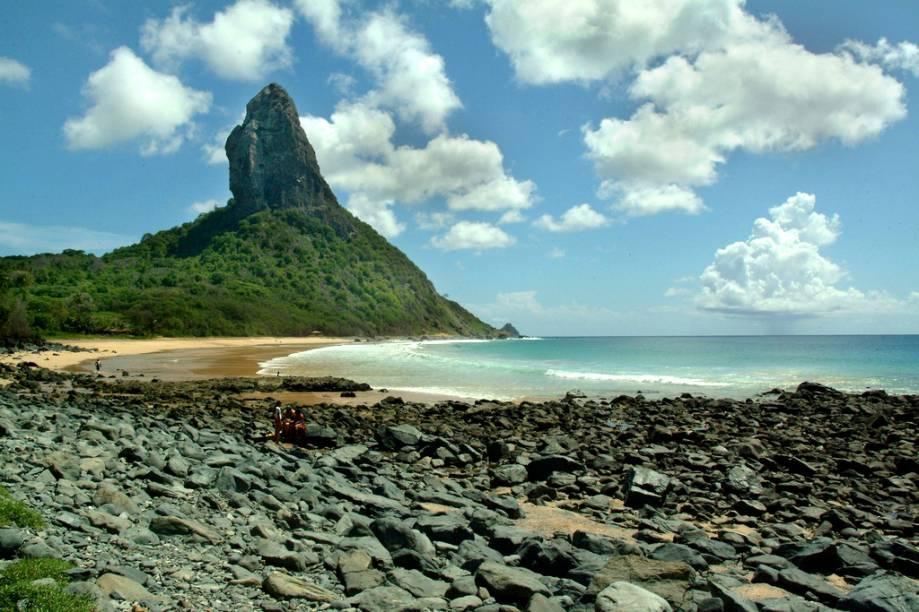 """<a href=""""http://viajeaqui.abril.com.br/estabelecimentos/br-pe-fernando-de-noronha-atracao-praia-da-conceicao""""><strong>Praia da Conceição</strong></a>Esta praia tem algo raro em Noronha: um bar pé na areia, o Duda Rei. Tome uma cervejinha e belisque um queijo coalho grelhado enquanto avista o Morro do Pico, faça uma caminhada pela extensa faixa de areia e, se a maré estiver baixa, explore as piscinas naturais que se formam no lado direito da praia. De abril a novembro, o mar fica calmo, mas de dezembro a março a praia é dos surfistas, com ondas de 1,5 metro. Sorte de quem estiver hospedado na Vila do Trinta ou na Vila dos Remédios, que consegue vir até a Praia da Conceição a pé."""