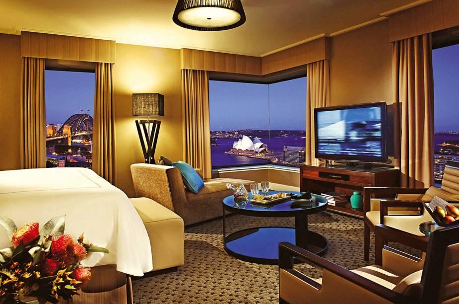 """A TV da Junior Suite do <a href=""""https://www.booking.com/hotel/au/four-seasons-sydney.pt-br.html?aid=332455&sid=d98f25c4d6d5f89238aebe98e11a09ba&dest_id=-1603135&dest_type=city&group_adults=2&group_children=0&hapos=1&hpos=1&no_rooms=1&sr_order=popularity&srepoch=1569951938&srpvid=56a97ce059320025&ucfs=1&from=searchresults;highlight_room=#hotelTmpl"""" target=""""_blank"""" rel=""""noopener""""><strong>Four Seasons Sydney</strong></a> pode até ser full HD, ter a maior seleção de canais a cabo ever, som Dolby, o diabo, mas o que de fato emociona, prende e hipnotiza é a vista das janelas para nada menos do que a <a href=""""http://viagemeturismo.abril.com.br/atracao/sydney-opera-house/"""" target=""""_blank"""" rel=""""noopener"""">Ópera</a> e a ponte Harbour, dois supercartões-postais da <a href=""""http://viagemeturismo.abril.com.br/paises/australia-2/"""" target=""""_blank"""" rel=""""noopener"""">Austrália</a>. O arrebatamento é tamanho que você até esquece que a mobília dos quartos está um pouco cansada e que o wi-fi é pago."""