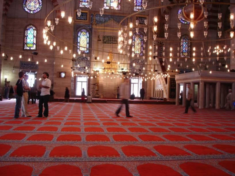 """<strong>Sala de Orações</strong>Parte fundamental na composição arquitetônica das mesquitas, a sala de orações não dispõe de cadeiras, como as igrejas cristãs, sendo muitas vezes acompanhadas por tapetes. A parede <em>qibla </em>- sempre orientada para Meca, o <em>mihrab </em>(nicho que indica a direção das orações) e o <em>minbar</em> (púlpito com degraus, à direita do <em>mihrab</em>) são elementos importantes que se encontram dentro de salas de orações, como esta, na mesquita de Solimão, em <a href=""""http://viajeaqui.abril.com.br/cidades/turquia-istambul"""" rel=""""Istambul """" target=""""_blank"""">Istambul </a>"""