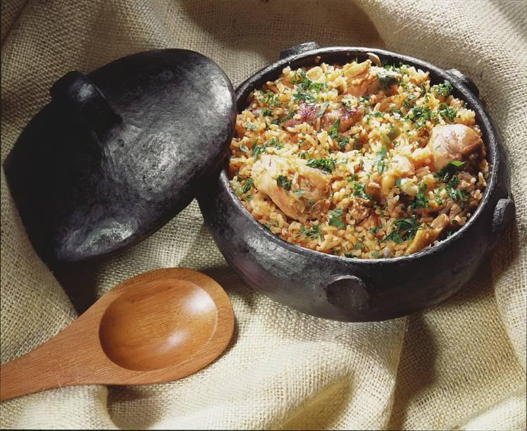 <strong>Galinhada</strong> Servida, geralmente, em eventos especiais, é um arroz reforçado com pedaços de frango caipira. A mistura costuma ser refogada com pequi e cúrcuma e, por isso, ganha coloração alaranjada.