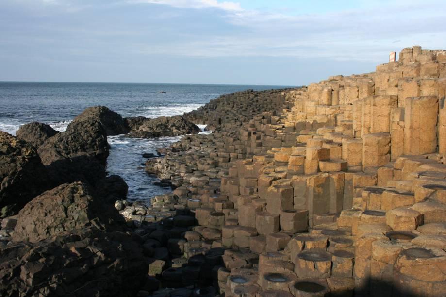 """<strong>Giants Causeway, Irlanda do Norte</strong> A curiosa formação que deu origem à lenda do gigante nada mais é que um conjunto de colunas de basalto. É a atração número 1 da Irlanda do Norte.<em><a href=""""https://www.booking.com/searchresults.pt-br.html?aid=332455&lang=pt-br&sid=eedbe6de09e709d664615ac6f1b39a5d&sb=1&src=index&src_elem=sb&error_url=https%3A%2F%2Fwww.booking.com%2Findex.pt-br.html%3Faid%3D332455%3Bsid%3Deedbe6de09e709d664615ac6f1b39a5d%3Bsb_price_type%3Dtotal%26%3B&ss=Irlanda+do+Norte%2C+%E2%80%8BReino+Unido&checkin_monthday=&checkin_month=&checkin_year=&checkout_monthday=&checkout_month=&checkout_year=&no_rooms=1&group_adults=2&group_children=0&from_sf=1&ss_raw=Irlanda+do+Norte+&ac_position=0&ac_langcode=xb&dest_id=1114&dest_type=region&search_pageview_id=b78a7774475204af&search_selected=true&search_pageview_id=b78a7774475204af&ac_suggestion_list_length=2&ac_suggestion_theme_list_length=0&district_sel=0&airport_sel=0&landmark_sel=0&map=1"""" target=""""_blank"""" rel=""""noopener"""">Busque hospedagens na Irlanda do Norte no Booking.com</a></em>"""