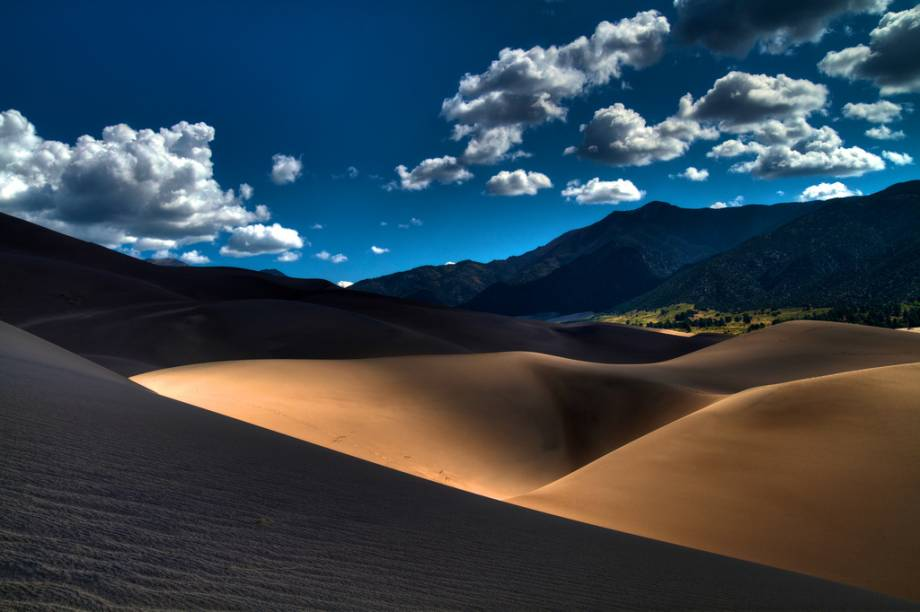 """<strong>Great Sand Dunes, Colorado</strong> O Great Sand Dunes National Park fica no Vale San Luis, a meio caminho entre Santa Fé, no Novo México, e Denver, Colorado. <a href=""""https://www.booking.com/searchresults.pt-br.html?aid=332455&lang=pt-br&sid=eedbe6de09e709d664615ac6f1b39a5d&sb=1&src=index&src_elem=sb&error_url=https%3A%2F%2Fwww.booking.com%2Findex.pt-br.html%3Faid%3D332455%3Bsid%3Deedbe6de09e709d664615ac6f1b39a5d%3Bsb_price_type%3Dtotal%26%3B&ss=Colorado%2C+%E2%80%8BEstados+Unidos&checkin_monthday=&checkin_month=&checkin_year=&checkout_monthday=&checkout_month=&checkout_year=&no_rooms=1&group_adults=2&group_children=0&from_sf=1&ss_raw=Colorado&ac_position=1&ac_langcode=xb&dest_id=2448&dest_type=region&search_pageview_id=dd77774d0bf3012d&search_selected=true&search_pageview_id=dd77774d0bf3012d&ac_suggestion_list_length=5&ac_suggestion_theme_list_length=0&district_sel=0&airport_sel=0&landmark_sel=0&map=1#map_opened"""" target=""""_blank"""" rel=""""noopener""""><em>Busque hospedagens em Colorado no Booking.com</em></a>"""