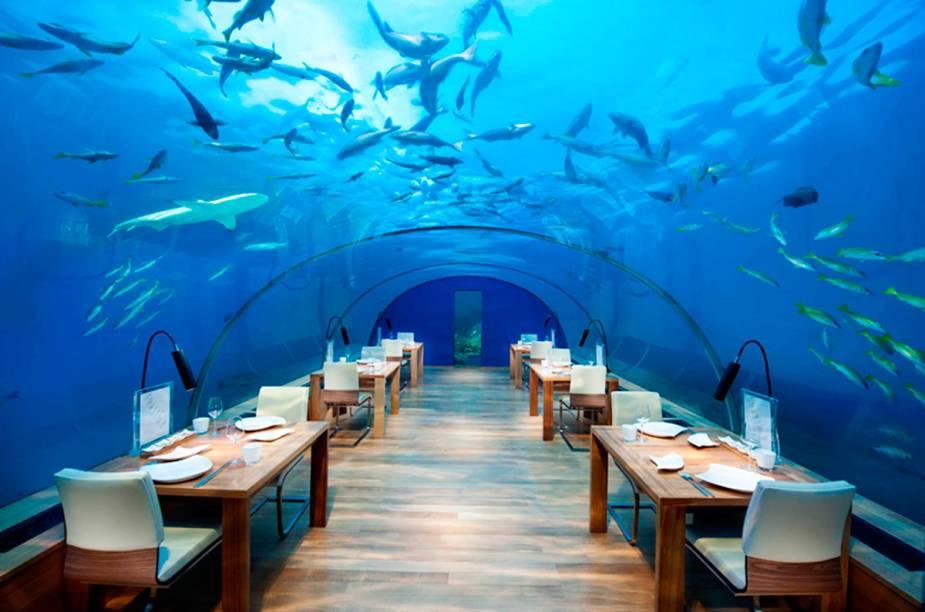 """O <a href=""""https://www.conradmaldives.com/dine/ithaa-undersea-restaurant/"""" target=""""_blank"""" rel=""""noopener"""">Ithaa</a> se localiza a 5 metros abaixo do nível do mar e oferece uma visão de 180° da vida marinha das profundezas. É importante reservar antes: a capacidade máxima é de 14 pessoas. A instalação, que é um túnel de acrílico fixado sobre uma estrutura metálica com silicone, funciona praticamente como um aquário ao contrário: os humanos ficam fechados, enquanto os peixes nadam livremente"""