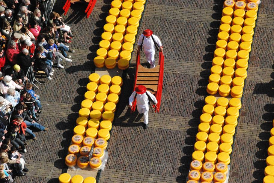 """<strong>Mercado de Queijos de Alkmaar, Holanda</strong> Senhores de avental branco e apressados carregadores dão o tom do mercado de queijos de Alkmaar, na <a href=""""http://viajeaqui.abril.com.br/paises/holanda"""" target=""""_blank"""" rel=""""noopener"""">Holanda</a>. Ele funciona em algumas sextas-feiras de abril a setembro, das 9h50 às 12h30, com explicações em holandês, alemão, francês e inglês. Uma tradição iniciada em 1593, a incessante movimentação para transporte, checagem e pesagem atrai milhares de turistas ao local. Cidades holandesas cujos queijos tornaram-se conhecidos mundo afora – caso de Edam e Gouda – também possuem atrações semelhantes"""