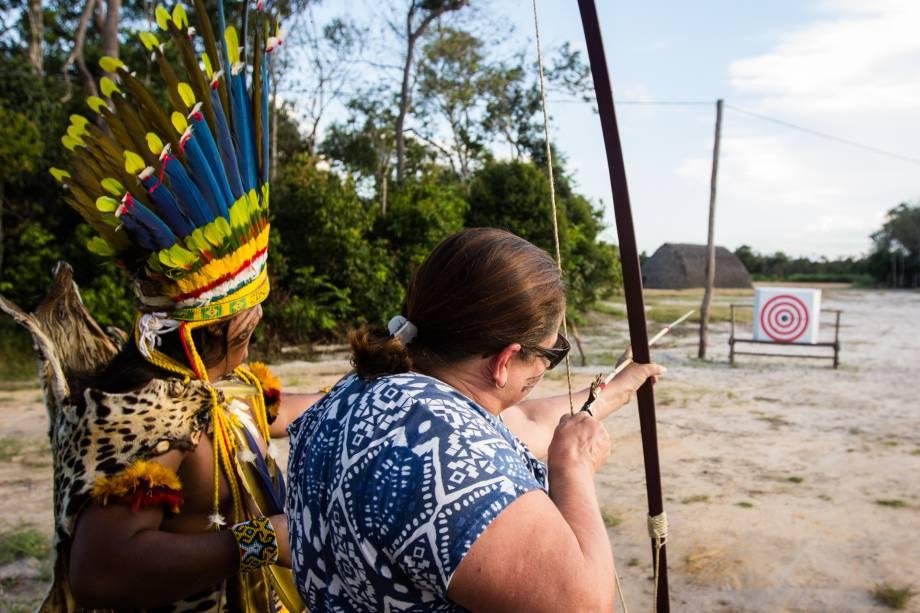 Além de vestir-se, pintar-se e comer como os indígenas, os turistas também têm aulas de arco-e-flecha tradicional da etnia.