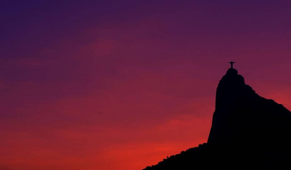 O Cristo Redentor, no Rio de Janeiro (RJ), envolto por pássaros e pelos tons do fim de tarde.