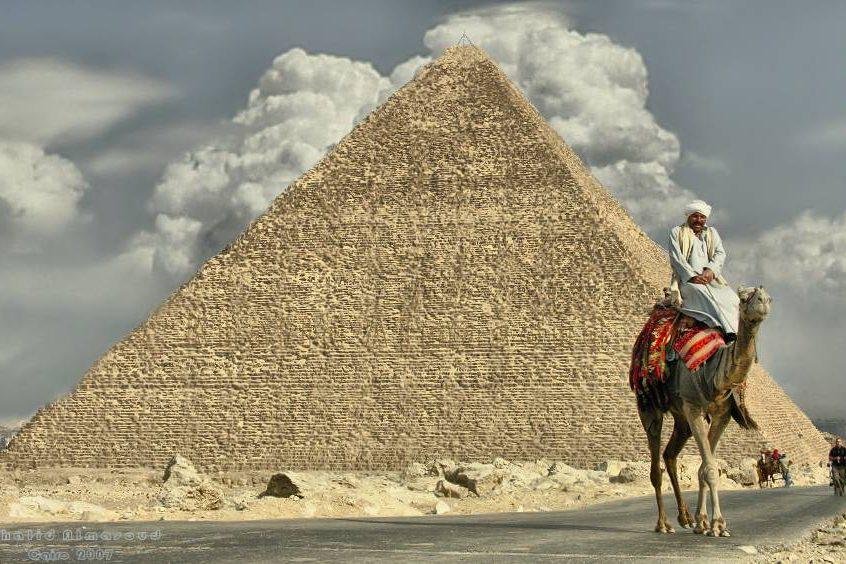 Beduínos ficam de prontidão por toda a área do sítio arqueológico, à espera de turistas interessados em passear de camelo com as pirâmides ao fundo