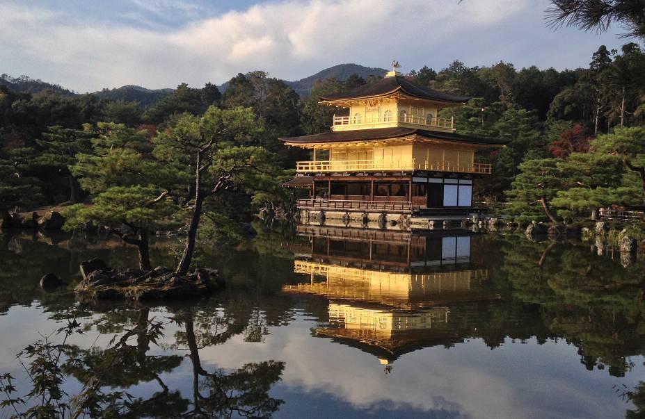 """<strong>Kinkaku-ji (Rokuon-ji) </strong> Apelidado de """"pavilhão dourado"""", é com certeza uma das construções mais bonitas da cidade. Antiga """"casa de repouso"""" do shogun (antigo chefe de estado) Ashikaga Yoshimitsu, foi transformado em templo budista após sua morte em 1408. Com os dois andares superiores inteiramente revestidos por folhas de ouro, o pavilhão literalmente brilha ao refletir a luz do sol, e tem o efeito maximizado pelo reflexo no lago a sua volta. A construção já foi destruída por dois incêndios, mas foi reconstruída a cada vez – a estrutura atual data de 1955."""