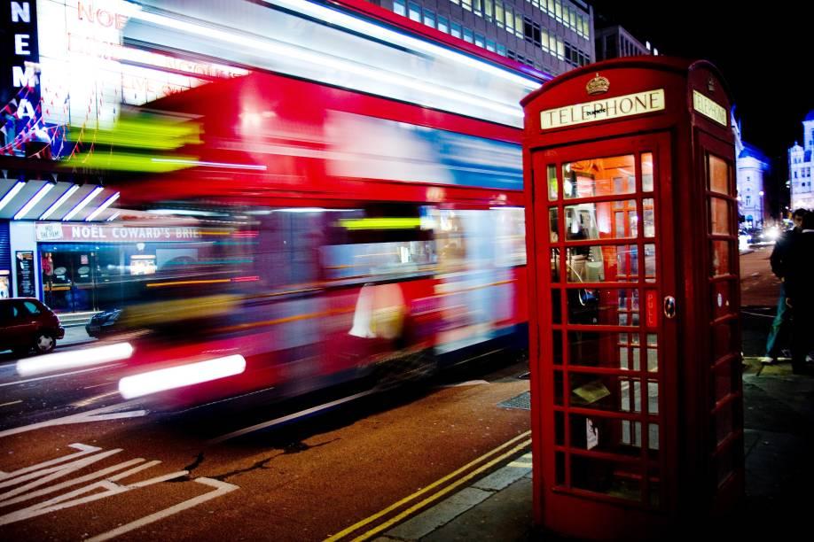 O icônicoRoutemaster, ónibus vermelho de dois andares, passando atrás de outro símbolo londrino: as cabines telefônicas vermelhas!
