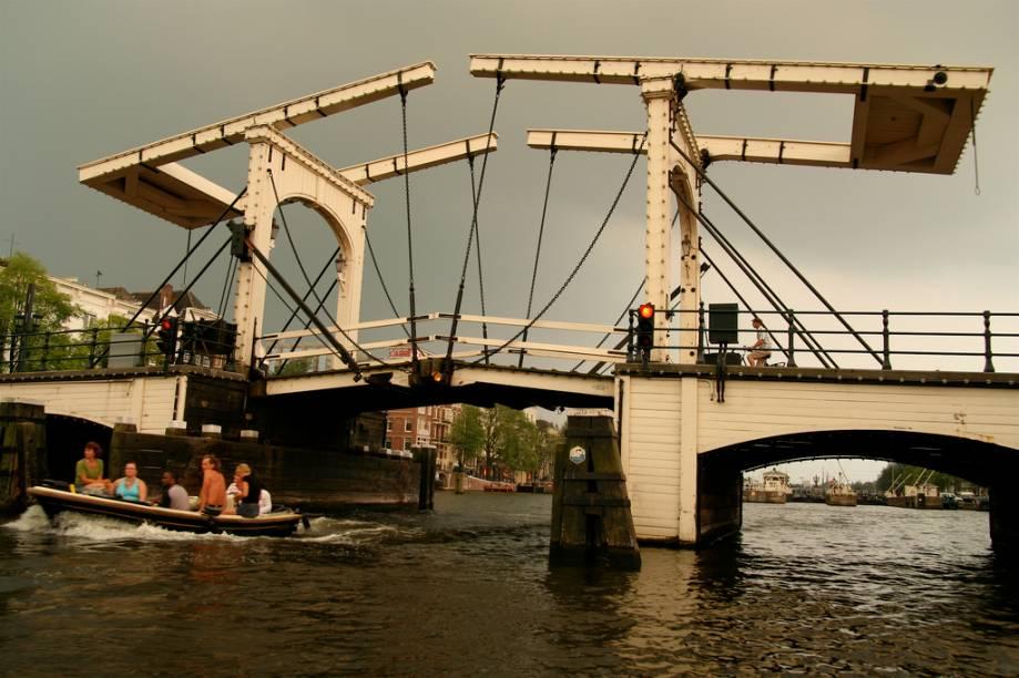 """<strong>Magere Brug, Amsterdã</strong>Com mais de 1200 pontes, <a href=""""http://viajeaqui.abril.com.br/cidades/holanda-amsterda"""" rel=""""Amsterdã """">Amsterdã </a>talvez seja a cidade com mais estruturas deste tipo em todo o mundo. A Magere Brug, a ponte magrela, era tão estreita que duas pessoas mal conseguiam se cruzar por ela ao atravavessa-la. A construção atual é de 1871"""
