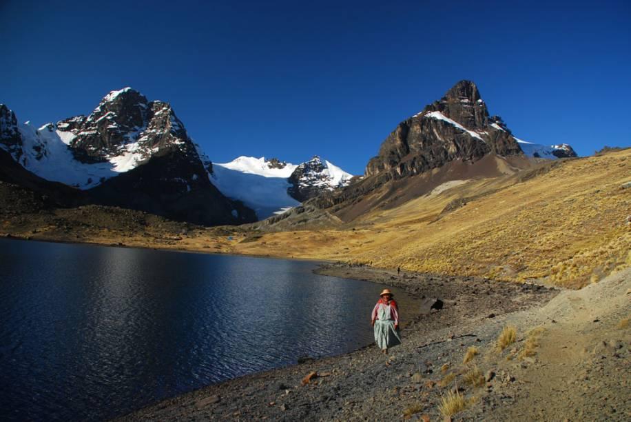 Mulher caminha na beira do lago, do Parque nacional de Condoriri, Bolívia