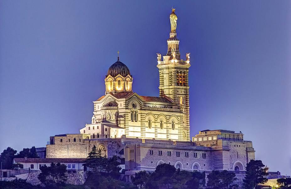 """A catedral de <a href=""""http://viajeaqui.abril.com.br/cidades/franca-marselha/"""" rel=""""Marselha"""">Marselha</a>,Notre-Dame de la Garde,tem arquitetura neo-bizantina e foi construída em 1864, no lugar de uma antiga igreja de mesmo nome, cuja fundação remonta a 1214"""
