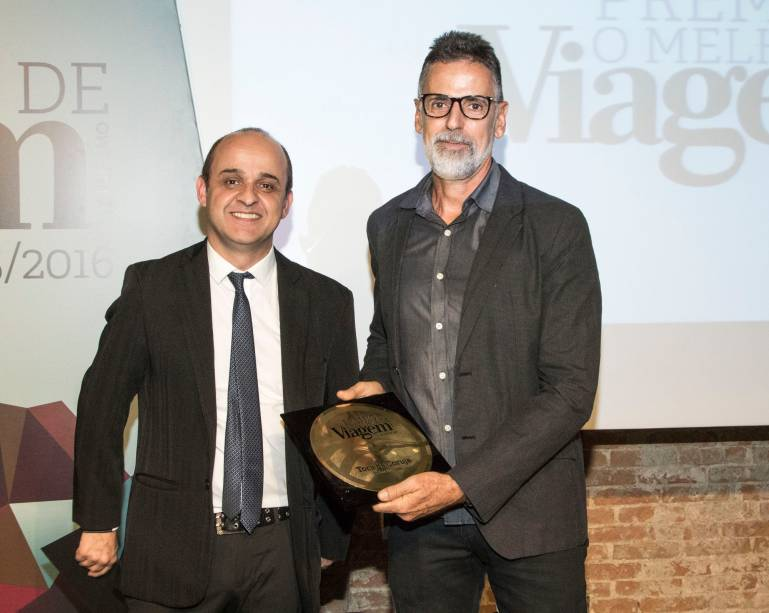 Luis Henrique Ribeiro, diretor da pousada Toca da Coruja, exibe o prêmio de melhor pousada; quem entregou a placa foi o editor-sênior da revista Viagem e Turismo, Almir de Freitas