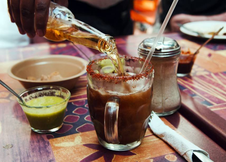 """<strong>6. Michelada – <a href=""""http://viajeaqui.abril.com.br/paises/mexico"""" rel=""""México """" target=""""_blank"""">México</a> </strong>                    Popular em todo México, o nome michelada vem de """"mi chela helada"""", ou """"minha cerveja gelada"""". Antes da popularização dos refrigeradores era comum colocar uns cubos de gelo na cerveja – e por que não um pouco de pimenta e limão, como tudo na culinária mexicana? Com o tempo, a receita foi se aperfeiçoando para incluir molho inglês e outros molhos prontos (como de soja e maggy), além de suco de tomate. Em algumas cidades, a mistura da michelada com molho de tomate se chama cubana, mas você não vai encontrar esse drink em Cuba. Em muitos bares na <a href=""""http://viajeaqui.abril.com.br/cidades/mexico-cidade-do-mexico"""" rel=""""Cidade do México"""" target=""""_blank"""">Cidade do México</a>, a mistura secreta da michelada perfeita é chamada de """"petróleo"""" e já fica pronta em uma jarra, para ser acrescentada à cerveja na hora de servir.                    <strong>Experimente em casa:</strong>as receitas variam muito e é tudo feito no """"olhômetro"""", mas aqui vai o princípio das coisas para ir treinando até achar sua mistura ideal: em um copo alto, faça uma borda de limão, sal e pimenta em pó. Sirva cerveja clara até três dedos abaixo da borda, acrescente suco de um limão pequeno, meia colher de chá de molho de pimenta, meia colher de chá de molho inglês e, se estiver se sentindo caribenho, um pouquinho de suco de tomate."""
