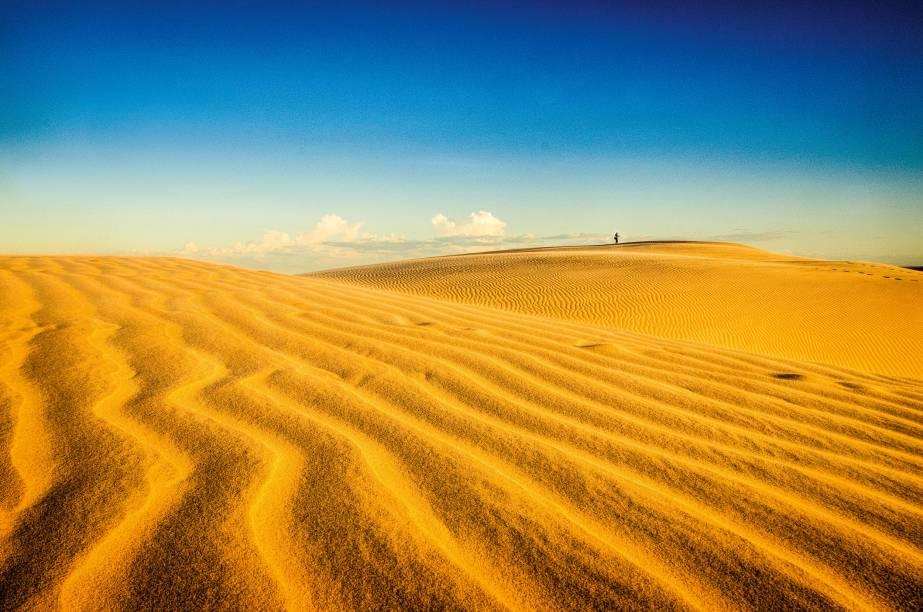 """<strong>Dunas do Rosado, Areia Branca</strong>    Cenários de filmes e novelas, as dunas se espelham pela Costa Branca do estado, onde o litoral e o sertão, invariavelmente, compartilham a mesma paisagem desértica. Na luz do fim de tarde, o formato do conjunto e a cor das dunas enchem de beleza, fácil, o cartão de memória de uma câmera    <strong><a href=""""http://viajeaqui.abril.com.br/materias/dunas-do-brasil-fotos"""" rel=""""+ 15 dunas do Brasil que merecem a sua visita"""" target=""""_blank"""">+ 15 dunas do Brasil que merecem a sua visita</a></strong>"""
