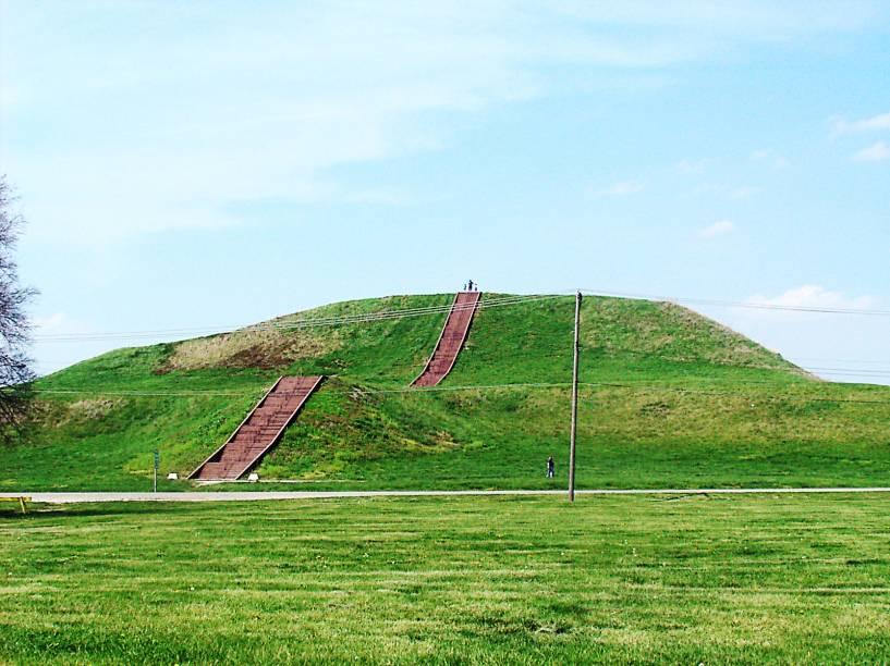 <strong>14. Monks Mound – Cahokia Mounds - EUA</strong>Sim, nos EUA também existem pirâmides! Localizada em Illinois, perto da cidade de St. Louis, esta da foto é apenas um dos mais de 80 edifícios escavados no Sítio Arqueológico Cahokia Mounds. Cahokia era o maior e mais influente assentamento urbano da região do rio Mississipi, que começou há mais de 1.500 anos. É considerado o maior e mais complexo sítio arqueológico a norte das cidades pré-colombianas no México. A Monks Mound tem 30m de altura e uma base de 291m de cada lado (a mesma base da pirâmide de Gizé, no Egito, porém bem mais baixa). Ela foi construída de terra, argila e madeira e possui uma rampa de acesso até seu topo. Porque os materiais utilizados são instáveis, a pirâmide sofreu diversos deslizamentos que fizeram com que sua base ficasse tão ampla já durante a construção.