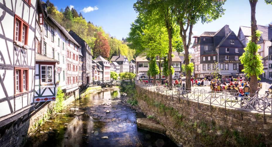 """Cercada pela cadeia montanhosa de Eifel, a cidade é repleta de colinas e construções que parecem ter saído da descrição perfeita dos contos de fadas europeus. Durante a Segunda Guerra Mundial, a cidade passou impune, o que deixou o centro bem preservado e as ruas estreitas e casas de madeira tais como eram há 300 anos. Lojinhas charmosas e cafés artesanais também estão entre os seus atrativos.<a href=""""http://www.booking.com/city/de/monschau-land-nordrhein-westfalen.pt-br.html?aid=332455&label=viagemabril-vilasalemanha"""" target=""""_blank"""" rel=""""noopener""""><em>Busque hospedagens em Monschau no Booking.com</em></a>"""