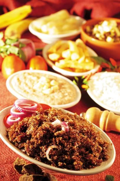 A carne é pilada manualmente com manteiga de garrafa, farinha e cebola roxa, e, depois, tostada na panela, no restaurante Paçoca de Pilão