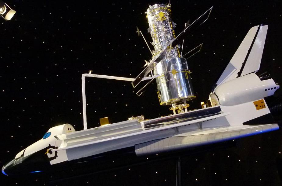 """Logo depois de assistir ao filme """"Hubble"""", o visitante é levado à uma área que detalha informações sobre os feitos do telescópio em órbita da Terra desde 1990. Na foto, uma réplica do Hubble, acoplado ao ônibus espacial Atlantis"""