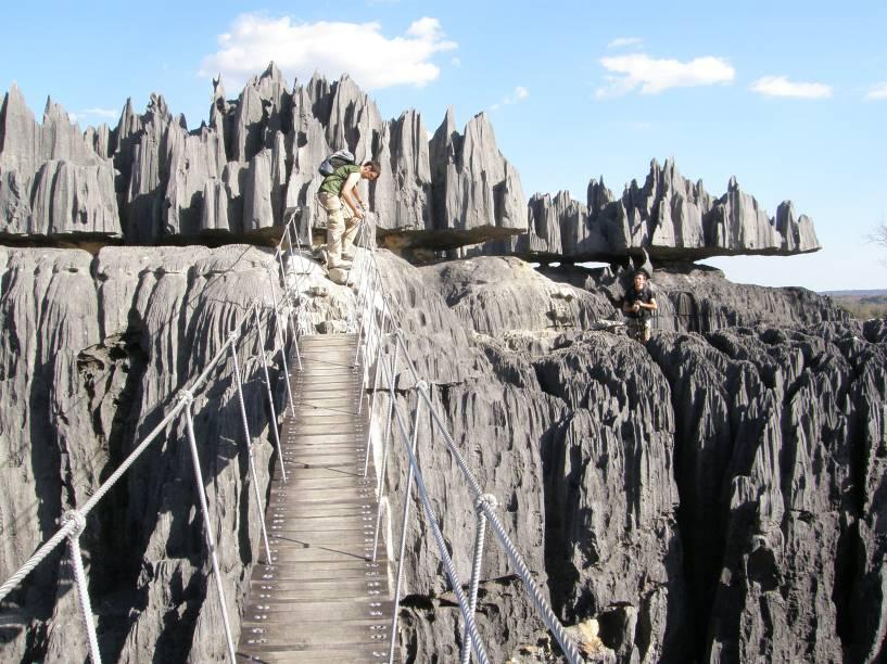 """<strong>Tsingy de Bemaraha, Madagascar</strong>O paredão de rocha que pode ser acessado por pontes móveis margeia o rio Manambolo. A floresta ao redor protege espécies de pássaros e lêmures em extinção.<a href=""""https://www.booking.com/searchresults.pt-br.html?aid=332455&lang=pt-br&sid=eedbe6de09e709d664615ac6f1b39a5d&sb=1&src=index&src_elem=sb&error_url=https%3A%2F%2Fwww.booking.com%2Findex.pt-br.html%3Faid%3D332455%3Bsid%3Deedbe6de09e709d664615ac6f1b39a5d%3Bsb_price_type%3Dtotal%26%3B&ss=Madagascar&ssne=Ilhabela&ssne_untouched=Ilhabela&checkin_monthday=&checkin_month=&checkin_year=&checkout_monthday=&checkout_month=&checkout_year=&no_rooms=1&group_adults=2&group_children=0&from_sf=1&ss_raw=Madagascar+&ac_position=0&ac_langcode=xb&dest_id=126&dest_type=country&search_pageview_id=7f327118397701ab&search_selected=true&search_pageview_id=7f327118397701ab&ac_suggestion_list_length=5&ac_suggestion_theme_list_length=0"""" target=""""_blank"""" rel=""""noopener""""><em>Busque hospedagens emMadagascar no Booking.com</em></a>"""