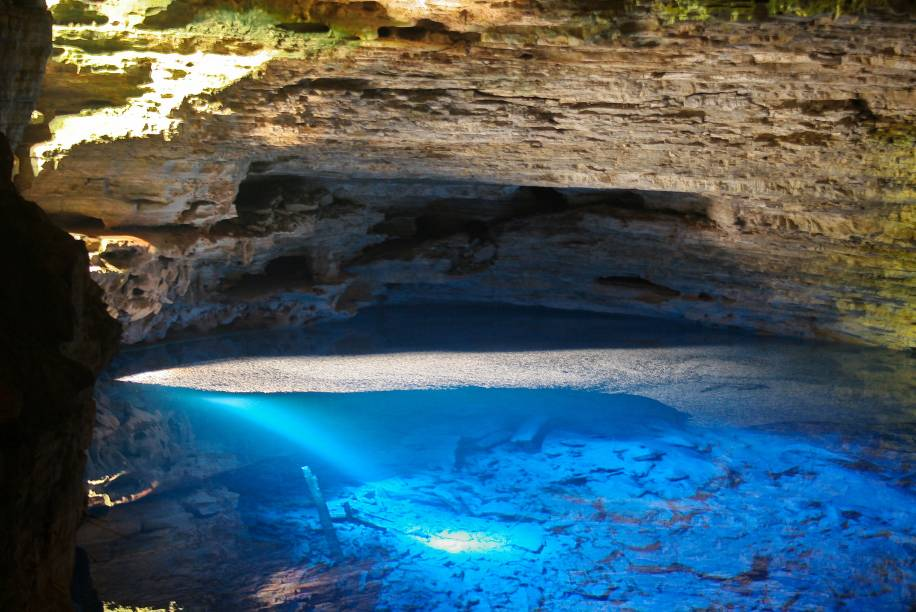 """<strong>10. Poço Encantado (Itaetê)</strong> Localizando dentro de uma caverna, o poço tem águas transparentes. Não é permitido entrar nas águas. O poço ganha tons azulados quando o sol incide por uma fenda, de abril a setembro, entre 10h e 12h.<em><a href=""""https://www.booking.com/searchresults.pt-br.html?aid=332455&sid=8118a1a04f2fb6081078124dc7c2384f&sb=1&src=index&src_elem=sb&error_url=https%3A%2F%2Fwww.booking.com%2Findex.pt-br.html%3Faid%3D332455%3Bsid%3D8118a1a04f2fb6081078124dc7c2384f%3Bsb_price_type%3Dtotal%26%3B&ss=Chapada+Diamantina%2C+Brasil&is_ski_area=&checkin_monthday=&checkin_month=&checkin_year=&checkout_monthday=&checkout_month=&checkout_year=&no_rooms=1&group_adults=2&group_children=0&map=1&b_h4u_keep_filters=&from_sf=1&ss_raw=Chapada+Diamantina&ac_position=0&ac_langcode=xb&dest_id=5235&dest_type=region&place_id_lat=-12.670709&place_id_lon=-41.43712&search_pageview_id=1b048a1f08110174&search_selected=true&search_pageview_id=1b048a1f08110174&ac_suggestion_list_length=5&ac_suggestion_theme_list_length=0#map_closed"""" target=""""_blank"""" rel=""""noopener"""">Busque hospedagens na Chapada Diamantina</a></em>"""